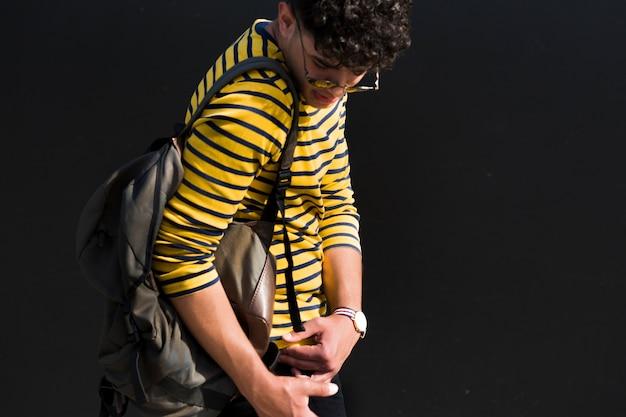 Jovem macho étnico com cabelo encaracolado e mochila na camisa listrada, olhando para baixo Foto gratuita
