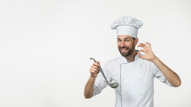 Jovem macho segurando a sopa de concha fazendo saboroso sinal isolado no fundo branco Foto gratuita