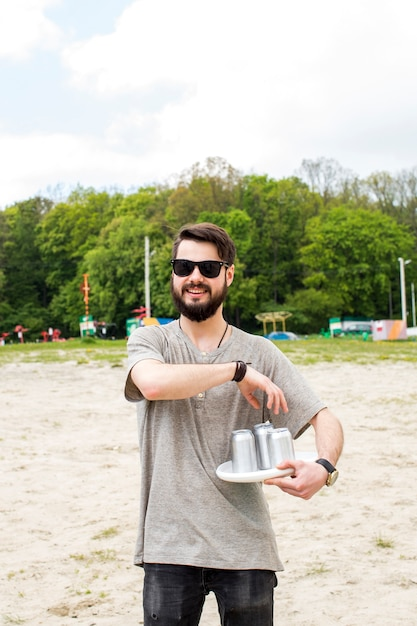 Jovem, macho, segurando, latas cerveja Foto gratuita