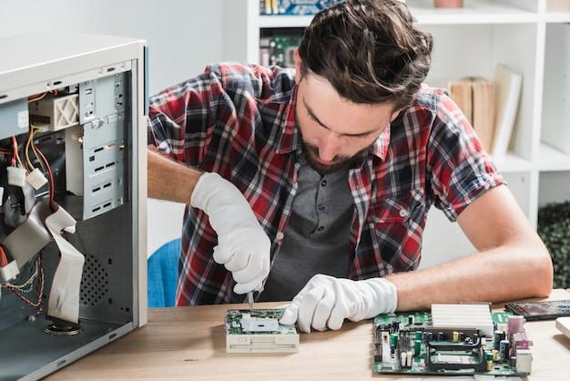 Jovem, macho, técnico, desgastar, luvas, afixando, computador, motherboard, com, chave fenda Foto gratuita
