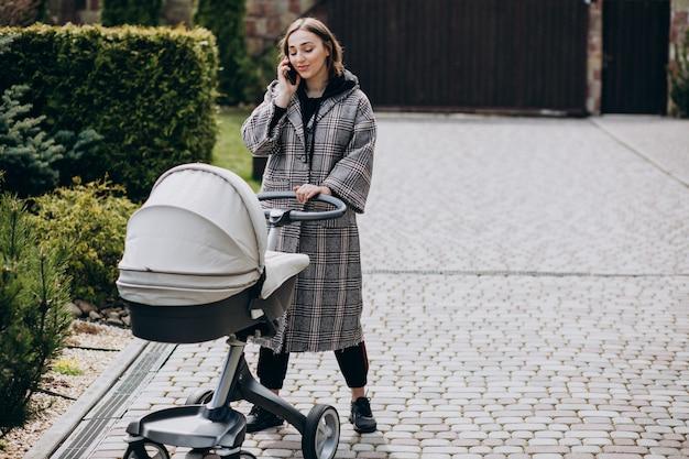 Jovem mãe andando com carrinho de bebê no parque e falando ao telefone Foto gratuita