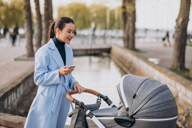 Jovem mãe andando com carrinho de bebê no parque Foto gratuita