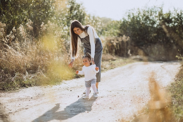 Jovem mãe andando com seu bebê no campo Foto gratuita