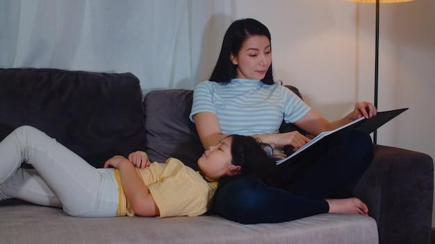 Jovem mãe asiática ler contos de fadas para sua filha em casa. a família chinesa feliz relaxa com a menina adolescente que dorme ao escutar contos que encontram-se na cama no quarto na casa moderna na noite. Foto gratuita