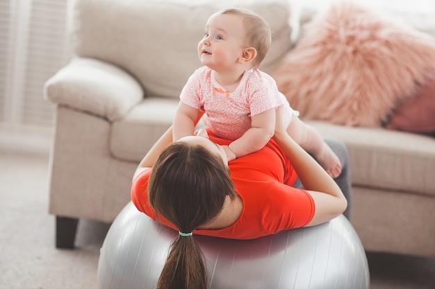 Jovem mãe bonita malhando com seu filho pequeno em casa Foto Premium