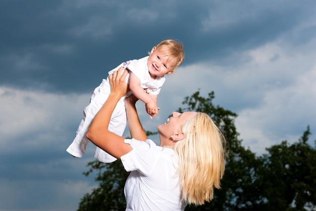 Jovem mãe brincando com seu bebê em um clima de tempestade Foto Premium