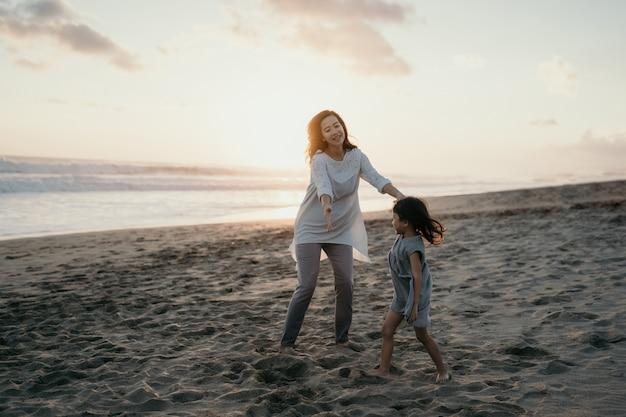 Jovem mãe brincando com sua filha à beira-mar Foto Premium