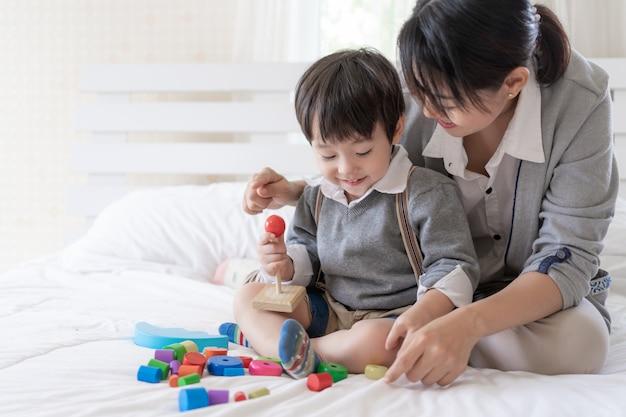 Jovem mãe brincar com o filho adorável no quarto Foto gratuita