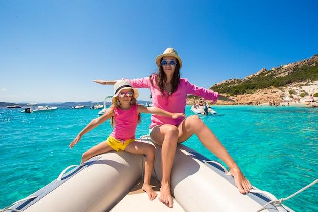 Jovem mãe com filha adorável desfrutar de férias no barco Foto Premium