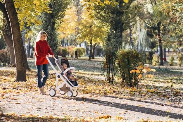 Jovem mãe com filha bebê andando no parque no outono Foto gratuita