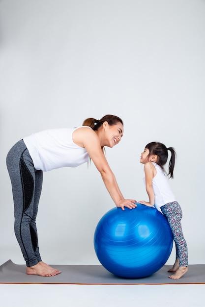 Jovem mãe com filha pequena exercício na bola de fitness Foto gratuita