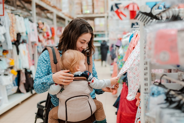 Jovem mãe com filho bebê às compras no supermercado Foto Premium
