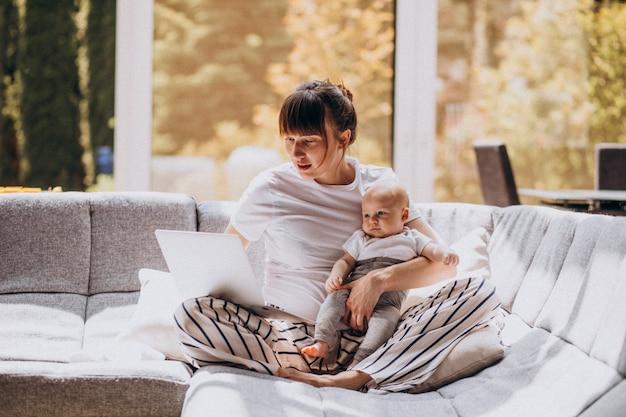 Jovem mãe com o filho dela, trabalhando em casa em um computador Foto gratuita