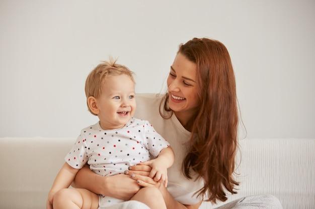 Jovem mãe com seu filho pequeno de um ano de pijama são relaxantes Foto gratuita
