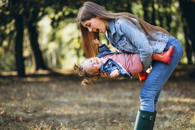 Jovem mãe com sua filha em um parque de outono Foto gratuita