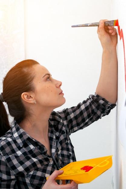 Jovem mãe de cabelos escuros na camisa xadrez desenha em uma parede branca Foto Premium
