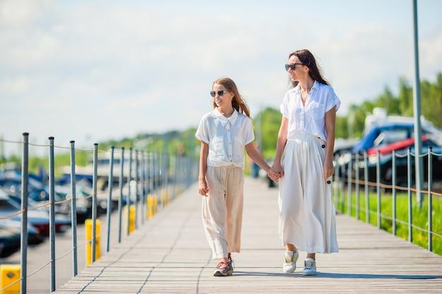 Jovem mãe e filha no porto no verão Foto Premium