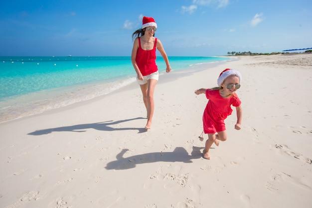 Jovem mãe e filha se divertir na praia tropical Foto Premium