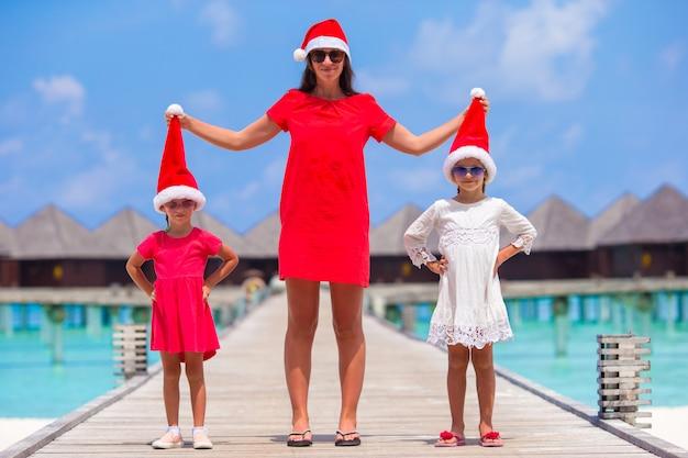 Jovem mãe e meninas no chapéu de papai noel Foto Premium