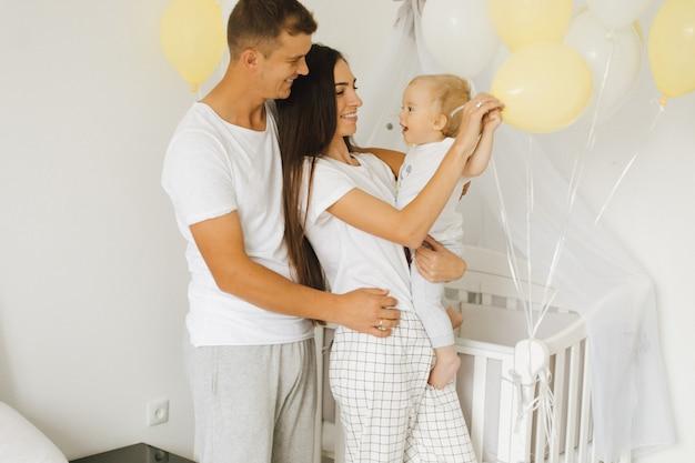 Jovem mãe e pai se alegrar com seu filho pequeno Foto gratuita