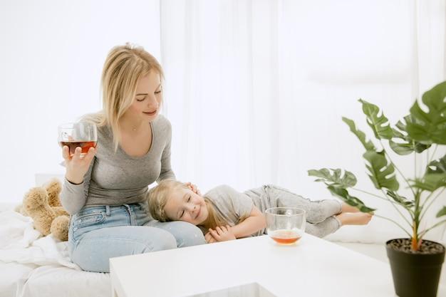 Jovem mãe e sua filha em casa na manhã ensolarada. cores pastel suaves. tempo feliz para a família no fim de semana. conceito de dia das mães. conceitos de família, amor, estilo de vida, maternidade e momentos ternos. Foto gratuita