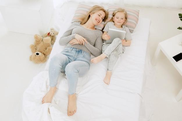 Jovem mãe e sua filha em casa na manhã ensolarada. cores pastel suaves. tempo feliz para a família no fim de semana. Foto gratuita