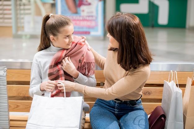 Jovem mãe experimentando um novo lenço de caxemira rosa na filha enquanto discute a compra após as compras Foto Premium