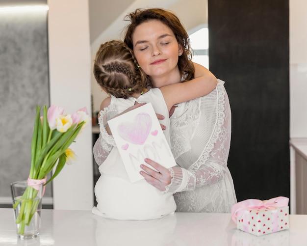 Jovem, mãe filha, abraçando, um ao outro, segurando, cartão cumprimento, ligado, dia mãe Foto gratuita