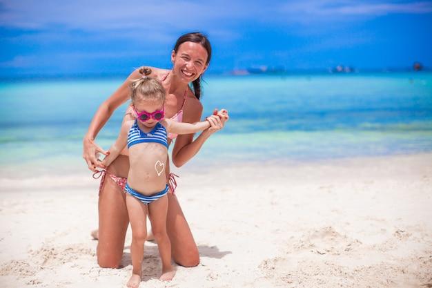 Jovem mãe linda e sua adorável filha se divertir na praia tropical Foto Premium