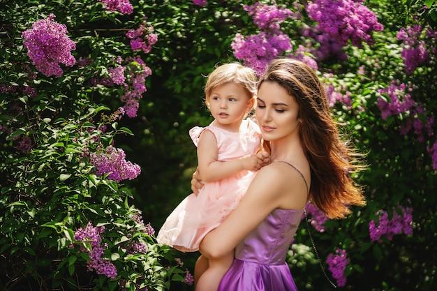 Jovem mãe linda mantém sua filha nos braços. conceito de dia das mães copie o espaço Foto Premium
