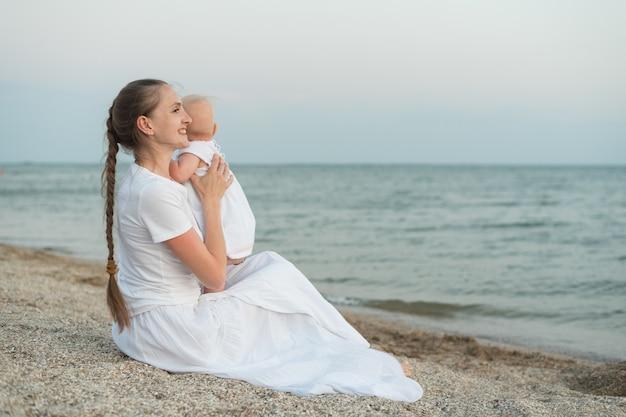 Jovem mãe linda sentada na praia e abraços bebê. Foto Premium