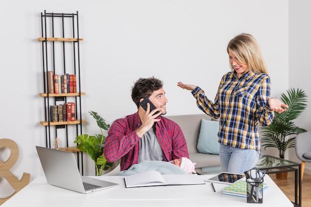 Jovem, mãe, olhar, pai, com, bebê, falando telefone Foto gratuita