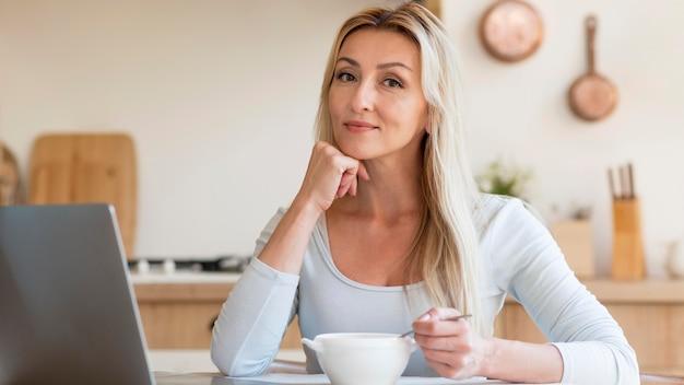 Jovem mãe posando enquanto trabalhava e tomando café da manhã em casa Foto gratuita
