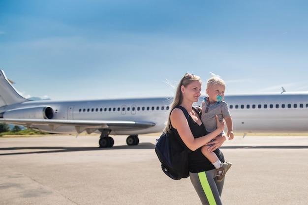 Jovem, mãe, segurando, dela, filho bebê, ligado, a, avião, e, céu azul, em, a, aeroporto Foto Premium