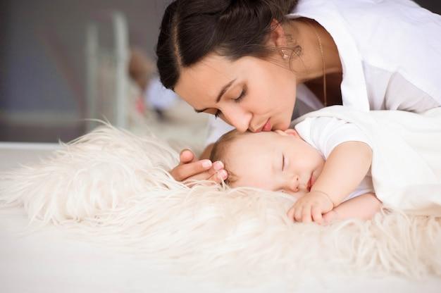 Jovem, mãe, segurando, ternamente, seu, recém-nascido, menino bebê Foto Premium