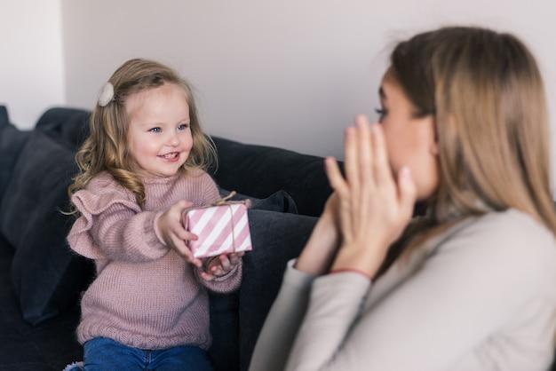 Jovem mãe sentada no sofá em casa recebeu uma surpresa da filha olhando o presente com espanto no dia das mães Foto gratuita