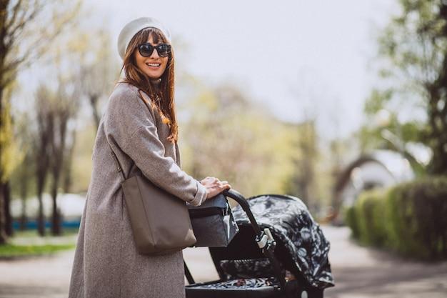 Jovem, mãe, sentando, com, carruagem bebê, parque Foto gratuita