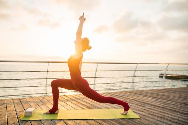 Jovem magro e atraente fazendo ioga pela manhã, no nascer do sol, à beira-mar Foto gratuita