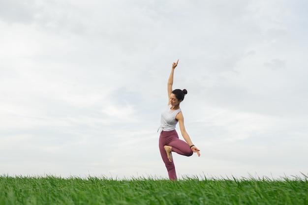 Jovem magro fazendo ioga ao ar livre em um campo verde Foto Premium