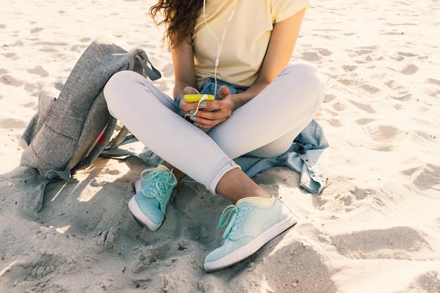 Jovem magro menina sentada na praia em jeans e uma camiseta amarela e ouvir música Foto Premium