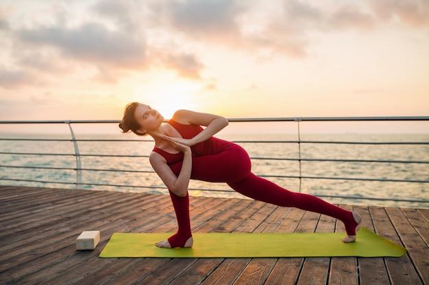 Jovem magro mulher atraente bonita fazendo yoga de manhã no nascer do sol pelo mar, estilo de vida saudável Foto gratuita