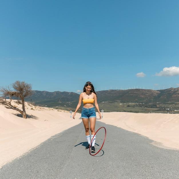 Jovem magro mulher rolar bambolê na estrada Foto gratuita