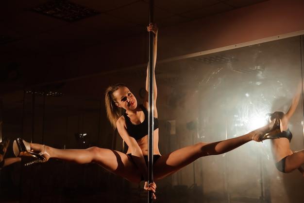Jovem magro pole dance mulher alongamento no interior brilhante. Foto Premium