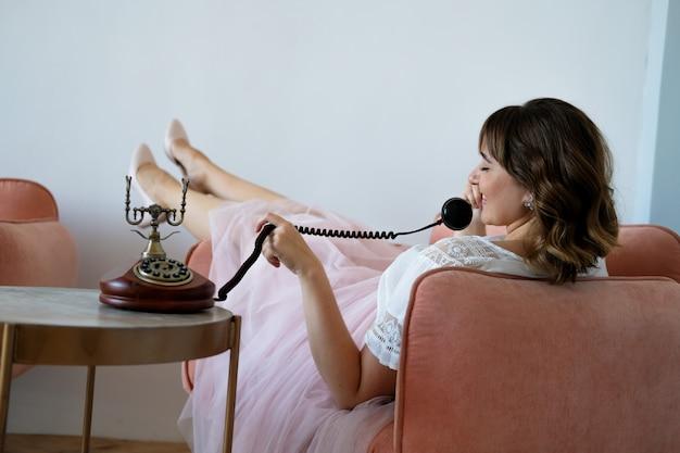 Jovem, mais mulher tamanho falando em um telefone retro sentado em uma cadeira Foto Premium