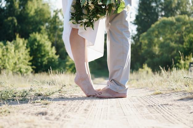Jovem marido e mulher com os pés descalços em uma estrada rural com um lindo buquê de flores Foto Premium