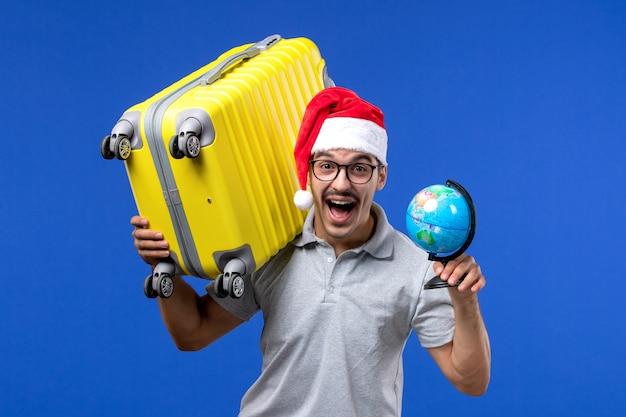 Jovem masculino carregando uma sacola amarela na viagem de férias do avião azul da mesa Foto gratuita