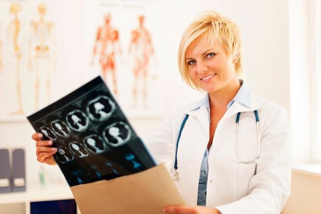Jovem médica abrindo envelope com resultado de tomografia cerebral Foto gratuita