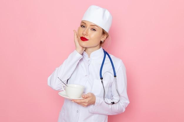 Jovem médica de terno branco com estetoscópio azul segurando a xícara de café de frente para o trabalho Foto gratuita