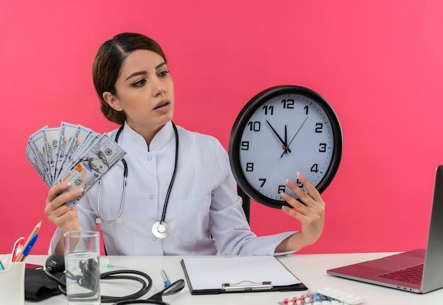 Jovem médica impressionada vestindo túnica médica com estetoscópio sentada na mesa de trabalho no computador com ferramentas médicas segurando dinheiro e olhando para o relógio de parede na mão rosa com espaço de cópia Foto gratuita
