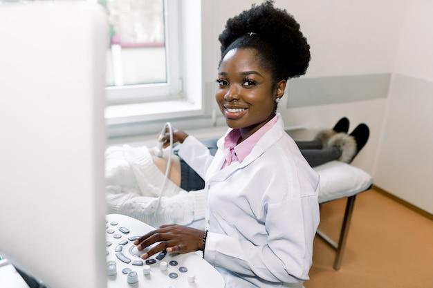 Jovem médico africano, olhando para a câmera e sorrindo, enquanto realiza a ultra-sonografia Foto Premium